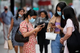 Shoppers stand together on Oxford Street, in London, Friday, July 24, 2020 New rules on wearing masks in England have come into…