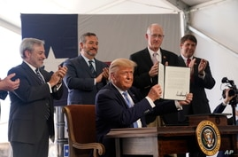 President Donald Trump holds up a permit for energy development after signing it during a visit to the Double Eagle Energy Oil…