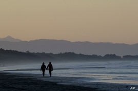 A couple walk along New Brighton Beach at sunset in Christchurch, New Zealand, Tuesday, June 9, 2020. New Zealanders enjoyed…