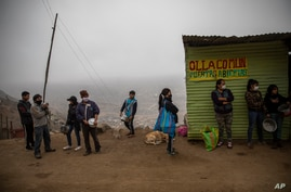 "Residents wait in line at a ""community pot,"" in the Nueva Esperanza neighborhood of Lima, Peru, Wednesday June 17, 2020. For…"
