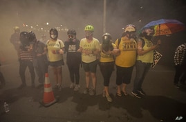 Members of the 'Wall of Moms' protest group lock arms as they are tear-gassed by federal officers during a Black Lives Matter…