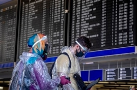 Passengers with protection gear walk past the flight board at the airport in Frankfurt, Germany, Friday, July 24, 2020. (AP…