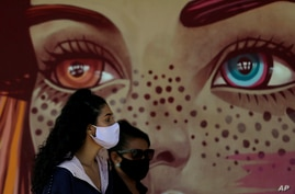 Women wear face masks amid the new coronavirus pandemic as they wait for a quick test at a COVID-19 testing site set up on a…