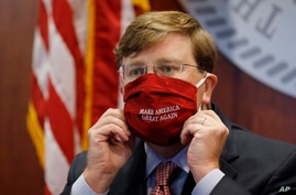 """Mississippi Gov. Tate Reeves adjusts his """"Make America Great Again,"""" face mask upon concluding his press briefing with members…"""
