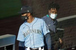 Seattle Mariners' Mallex Smith, left, and Dee Gordon, right, wear masks as they enter the dugout, Monday, July 20, 2020, during…