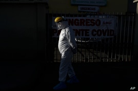 A health worker in full protective gear walks outside the Del Norte Hospital, which is treating COVID-19 patients exclusively,…