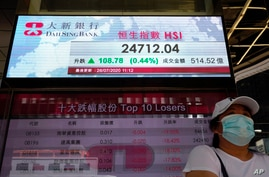 A woman wearing a face mask stands beneath a bank's electronic board showing the Hong Kong share index at Hong Kong Stock…