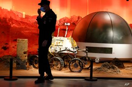 A security guard adjusts his mask near an exhibition of rovers and bio-domes on Mars in Beijing Thursday, July 23, 2020. China…