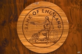 A wooden carving of the Bank of England logo is seen on a desk during a news conference by Bank of England governor Mark Carney…