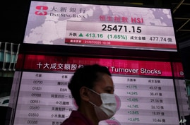 A woman wearing a face mask walks past a bank's electronic board showing the Hong Kong share index at Hong Kong Stock Exchange…
