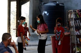 Children wear face masks while shopping at a grocery store during a lockdown imposed during the coronavirus pandemic, at Shati…