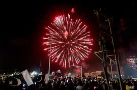 People gather to watch fireworks during the Independence Day celebrations, in Karachi, Pakistan, Friday, Aug. 14, 2020…