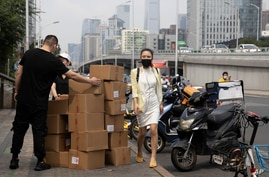 A woman wearing a mask walks past delivery workers moving boxes in Beijing on Aug. 20, 2020. U.S. and Chinese trade envoys…