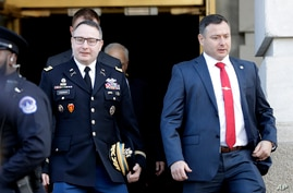 FILE - In this Nov. 19, 2019, file photo National Security Council aide Lt. Col. Alexander Vindman, left, walks with his twin…