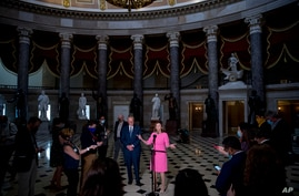 House Speaker Nancy Pelosi of Calif., center, accompanied by Senate Minority Leader Sen. Chuck Schumer of N.Y., left, speaks to…