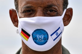 German Lieutenant colonel Samuel Mbassa wears a face mask with the flags of Israel and Germany at the airbase in Noervenich,…