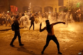A protester throws stones against the Lebanese riot police during anti-government protest following Tuesday's massive explosion.