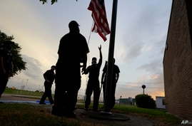 Port Arthur firefighters lower a U.S. flag at a post office at sunset as they wait for Hurricane Laura to make landfall,…
