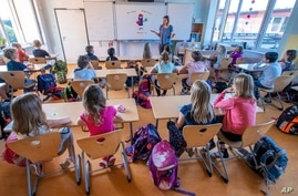 File---File picture taken Aug.3, 2020 shows teacher Francie Keller welcoming the pupils of class 3c in her classroom in the…
