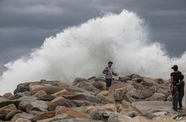 A tourist poses for a photo in front breaking waves before the expected arrival of Hurricane Lorena, in Los Cabos, Mexico,…