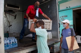 Cafeteria owner Miguel Sanchez, right, inspects his purchase as a porter loads his items into a courier service's truck, to…