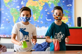 Nine years old boys Tom, left, and Patrizio wear face masks to protect against the coronavirus as they show a musical…