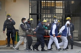 Inmates wearing white protective suits, and security agents, transport an inmate to a clinic at the Lurigancho prison on the…