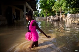 A girl wades towards her flooded home the day after the passing of Tropical Storm Laura in Port-au-Prince, Haiti, Monday, Aug…