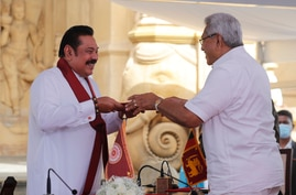 Sri Lanka's former President Mahinda Rajapaksa, left, receives appointment documents his younger brother, President Gotabaya…