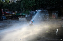 An anti-government protester, holding a Mapuche flag, is brought down by the jet spray of a police water cannon, in Santiago,…