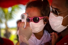 A little girl wearing a face mask amid the new coronavirus pandemic gets her temperature taken at a police checkpoint, at the…