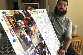 Roland Mack holds a poster with pictures and messages made by family members in memory of his sister, Chantee Mack, in District…