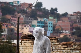 A state department health worker stands in full protective gear while recovering the body of a street vendor who was found at…
