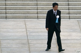 FILE - In this Aug. 6, 2020, file photo, Japanese Prime Minister Shinzo Abe walks off after delivering a speech during a…