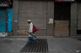 An Indian man walks past closed shops in a market during weekend lockdown to curb the spread of coronavirus  in Gauhati, India,…