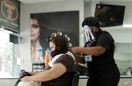 A hairstylist services a client at the Factory Fashion Beauty Salon in Panama City, Monday, Aug. 17, 2020. After nearly five…