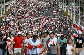 Belarusian opposition supporters with old Belarusian national flags rally in Minsk, Belarus, Sunday, Aug. 30, 2020. Tens of…