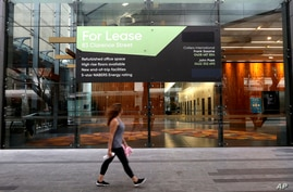 A woman walks past a lease sign at a commercial building in Sydney, Wednesday, Sept. 2, 2020. Australia's economy has suffered…
