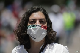 "A woman wears a face mask with text reading in Spanish ""AMLO, leave already,"" during a protest demanding the resignation of…"