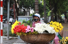 A flower vender wearing a face mask to protect against the coronavirus waits for customers in Hanoi, Vietnam, Monday, Aug. 3,…