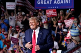 President Donald Trump stands on stage after speaking at a campaign rally at Smith Reynolds Airport, Tuesday, Sept. 8, 2020, in…