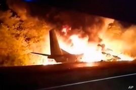 In this TV grab released by Ukraine's Emergency Situation Ministry, an AN-26 military plane bursts into flames after it crashed…