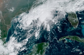 This GOES-16 GeoColor satellite image taken Saturday, Sept. 19, 2020, and provided by NOAA, shows Tropical Storm Beta, center, …
