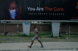 A man walk past an electronic billboard warning residents to wear face masks to protect against coronavirus, in Lagos Nigeria…