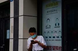 A resident wearing a mask to curb the spread of the coronavirus stand near a shuttered store that offered visa application…