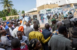 Security forces fire tear gas at people gathered outside a conference to discuss a transition to a civilian government in…