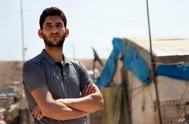 In this Sunday Sept. 1, 2019 photo, Syrian Abdel Hamid al-Yousef poses for a picture, at a displaced settlement near the…