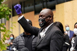 Attorney Ben Crump, representing George Floyd's family, raises a closed fist as he addresses the media after a hearing at the…