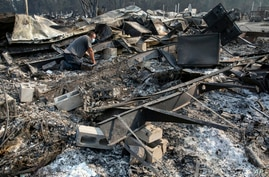 Jon Marshall looks through the debris of his home among the at Coleman Creek Estates mobile home park in Phoenix, Ore.,…