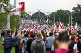Belarusian opposition supporters with old Belarusian national flags gather toward the Independence Palace, the residential of…